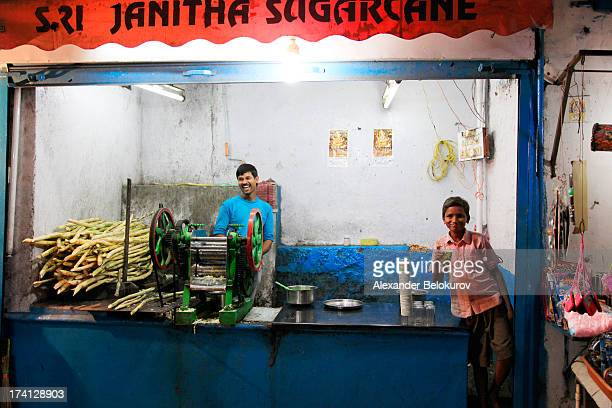 Smiling vendor of freshly pressed sugarcane juice standing behind old-style mechanical juice press in small street store in Hyderabad, India. Smiling...