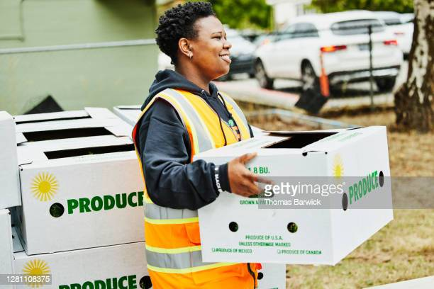 smiling volunteer holding csa box at community center - responsibility stock pictures, royalty-free photos & images