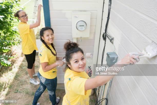 Smiling volunteers painting house