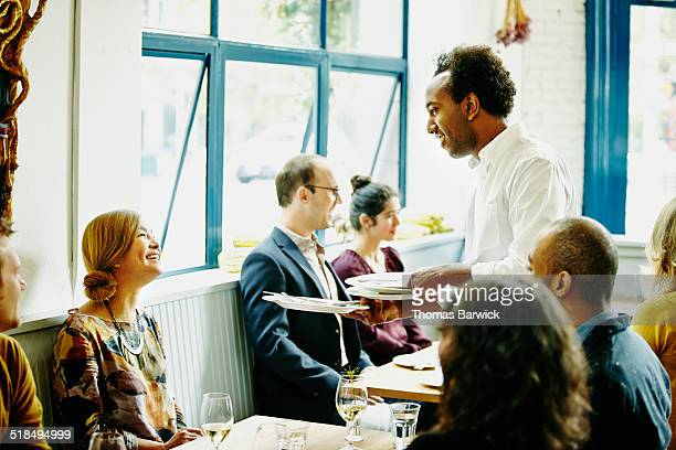 Smiling waiter in discussion with woman at table