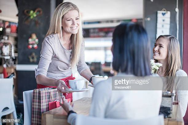 Smiling waitress serving cups of coffee in a coffee shop