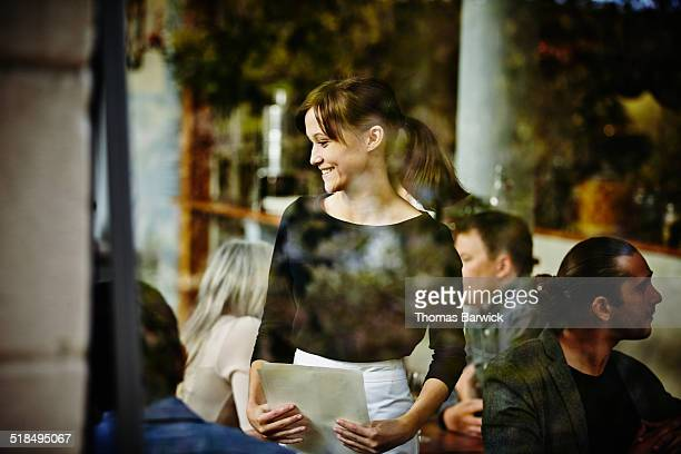 smiling waitress taking order view through window - wait staff stock pictures, royalty-free photos & images
