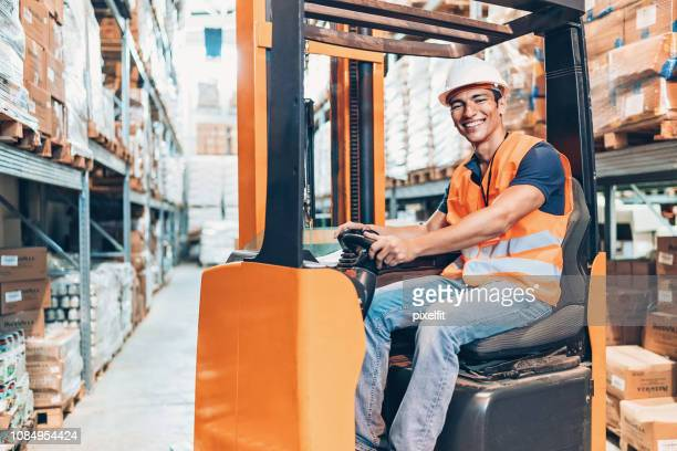 Smiling warehouse worker in a forklift