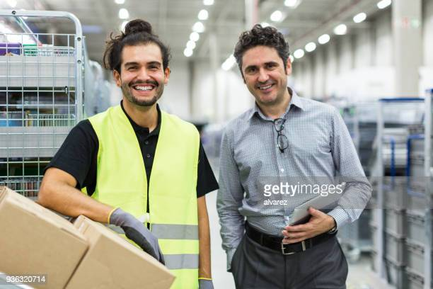 lächelnde lagerarbeiter mit vorarbeiter - bürojob stock-fotos und bilder