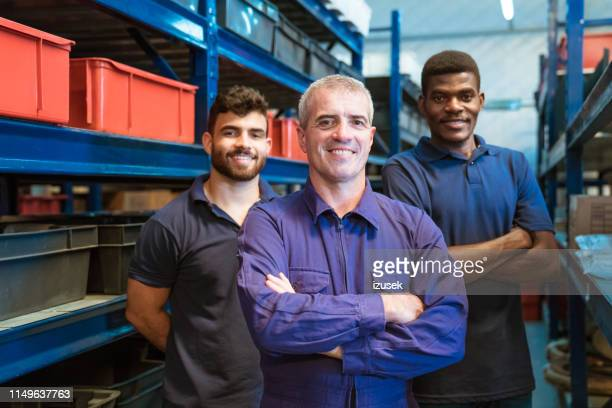 smiling warehouse workers standing in storage room - izusek stock pictures, royalty-free photos & images