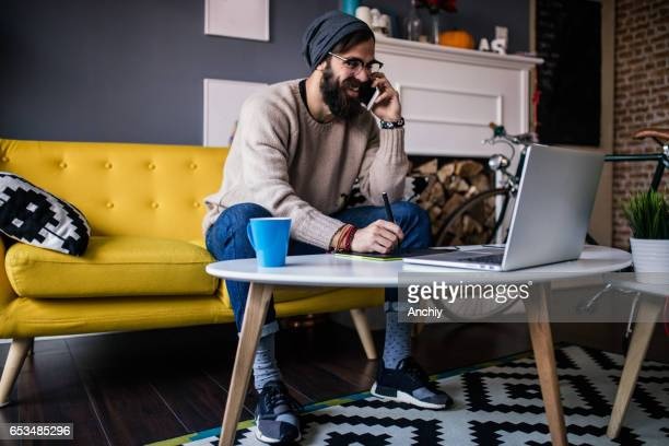 Smiling webdesigner working from his home office