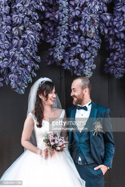 smiling wedding couple looking each other face to face while standing against wall - hochzeit fotos stock-fotos und bilder