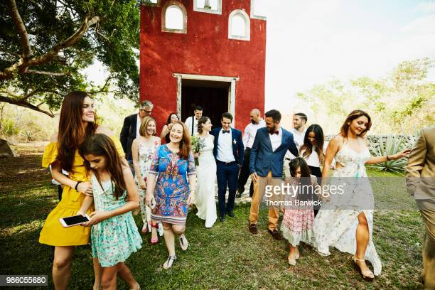 smiling wedding party walking to reception after wedding ceremony at chapel at tropical resort - wedding after party stock pictures, royalty-free photos & images