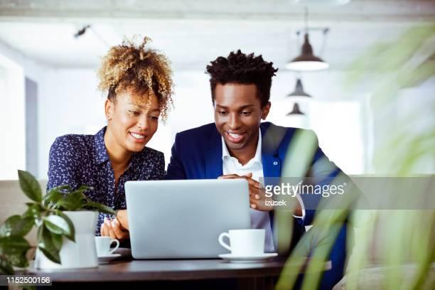 los trabajadores de cuello blanco sonriente que buscan laptop - izusek fotografías e imágenes de stock