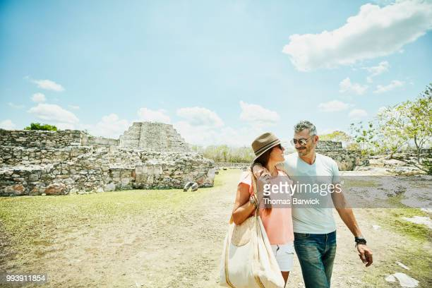 Smiling wife and husband with arms around each other exploring Mayapan ruins during vacation