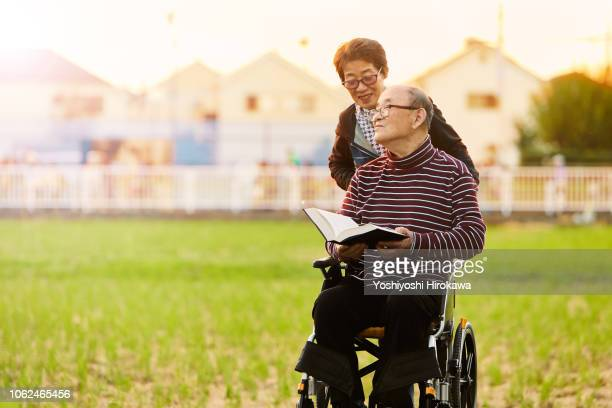 smiling wife assisted living with wheelchair,man has book on his hand - snapping the ball stock pictures, royalty-free photos & images