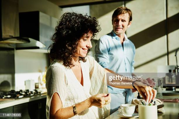 smiling wife in discussion with husband while sitting in kitchen - wife stock pictures, royalty-free photos & images