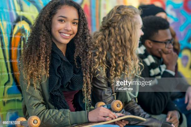 smiling with her skateboard - black girls stock photos and pictures