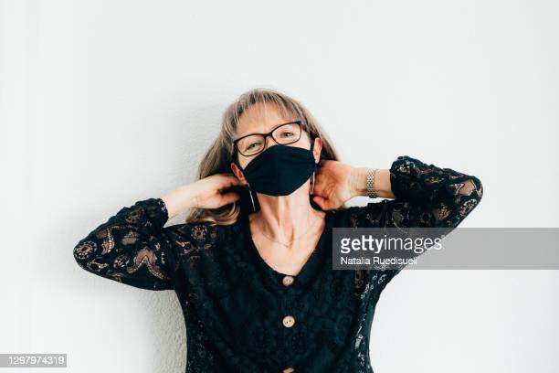 smiling woman 50-55 years old wearing a black colored mask and touching her hair. - 55 59 years stock pictures, royalty-free photos & images