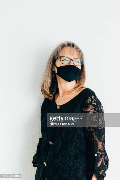 smiling woman 50-55 years old wearing a black colored mask. - 55 59 years stock pictures, royalty-free photos & images