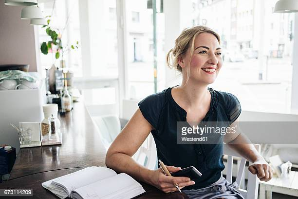 Smiling woman accounting in a cafe