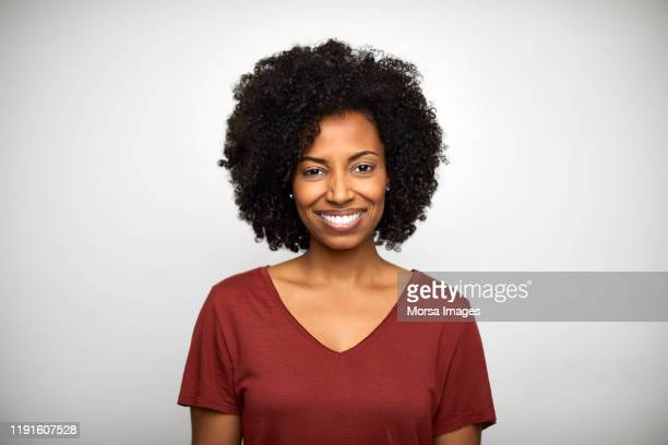 smiling woman against white background - black photos et images de collection
