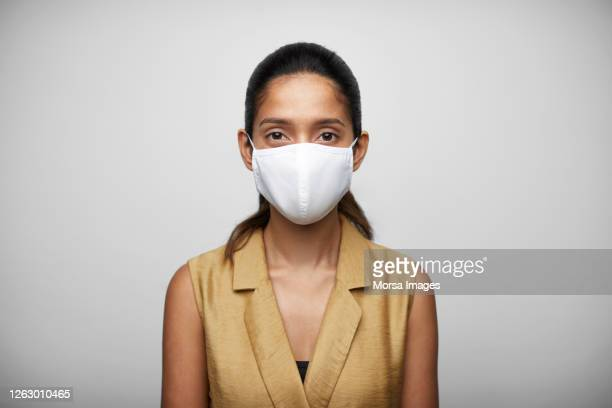 smiling woman against white background wearing n95 face mask. - waist up stock pictures, royalty-free photos & images