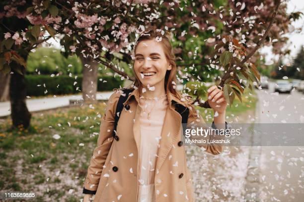 smiling woman among falling petals from tree in bloom - bloesem stockfoto's en -beelden