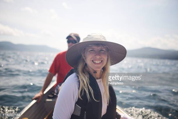 smiling woman and friend in canoe - heshphoto stock pictures, royalty-free photos & images
