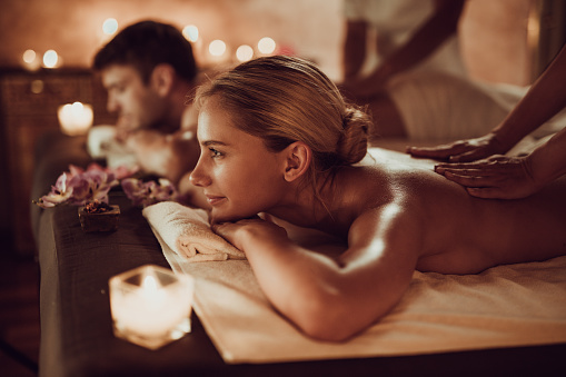Smiling woman and her boyfriend having back massage at the spa. 1051690008