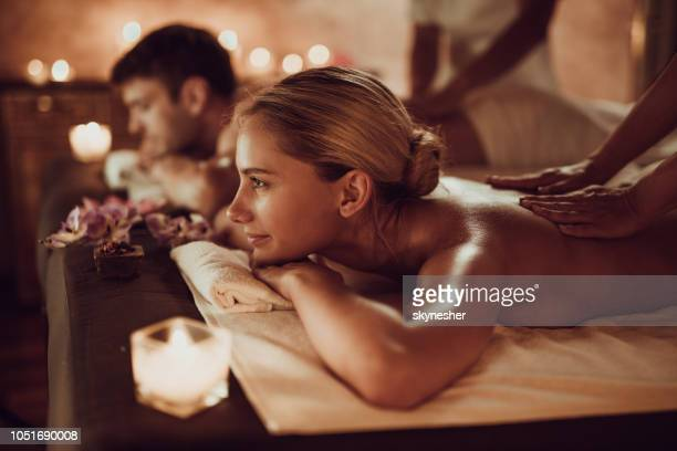smiling woman and her boyfriend having back massage at the spa. - massage therapist stock pictures, royalty-free photos & images