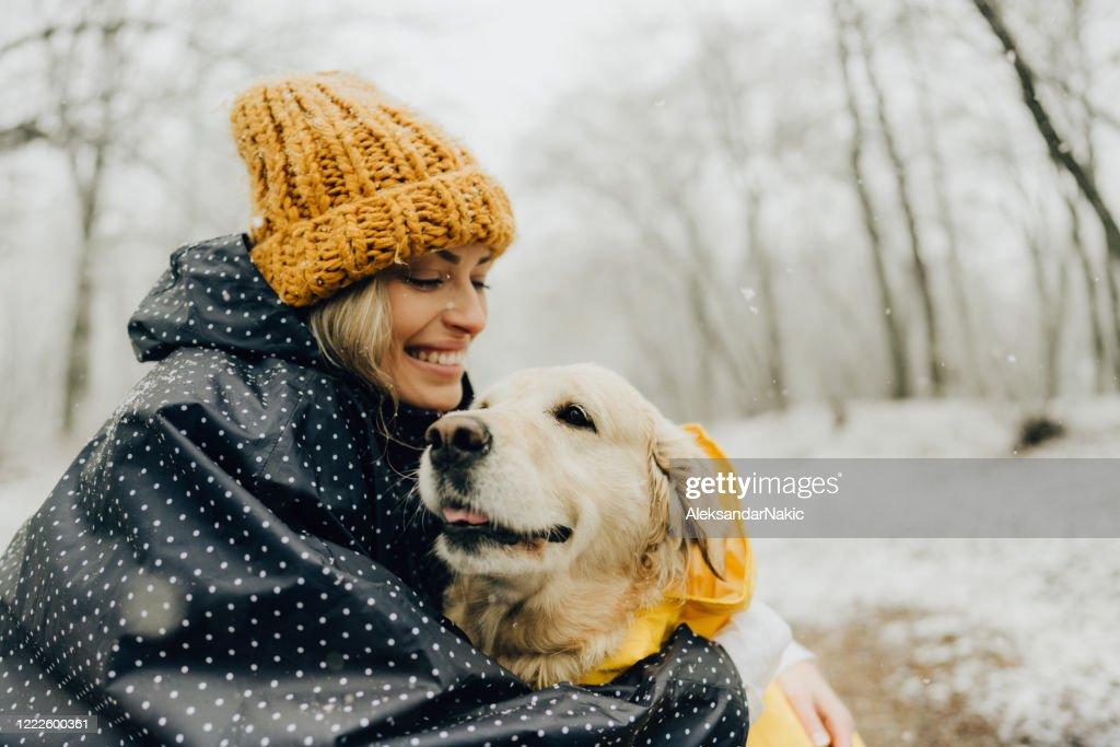 Glimlachende vrouw en haar hond in een sneeuwdag : Stockfoto