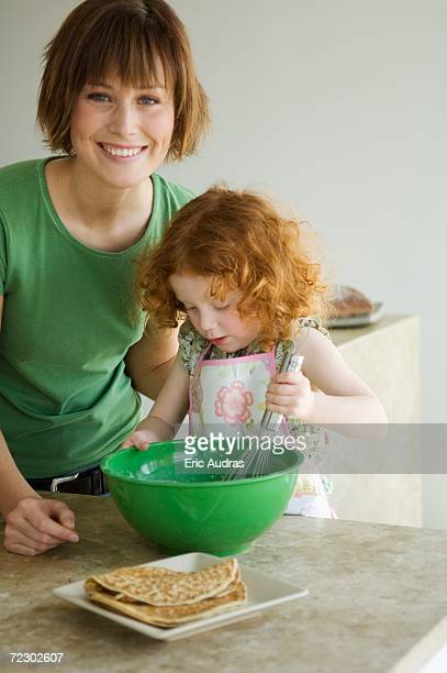 Smiling woman and little girl cooking
