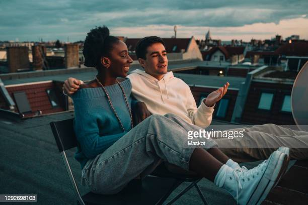smiling woman and man talking while sitting on building rooftop during sunset - einfaches leben stock-fotos und bilder