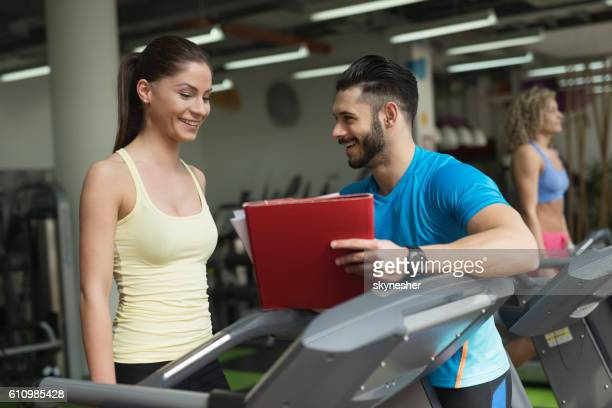 Smiling woman and personal trainer making exercise plan in gym.