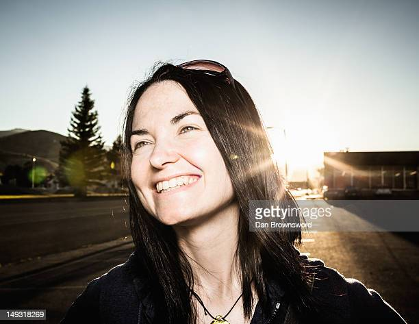 Smiling woman and sun flare outdoors