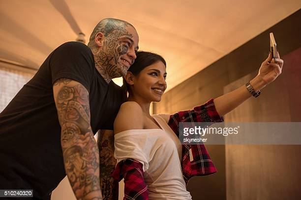 Smiling woman and tattoo artist taking selfie with cell phone.