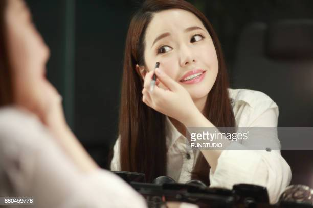 Smiling woman applying concealer on face