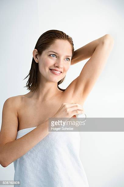 Smiling woman applying deodorant