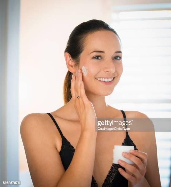 Smiling woman applying face cream to cheek in bathroom mirror