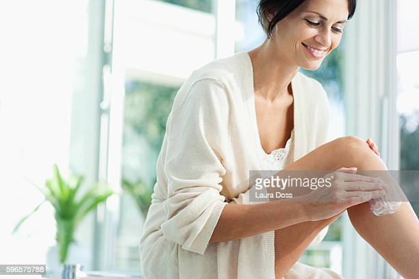 smiling woman applying lotion - older woman legs stock photos and pictures