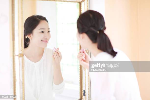Smiling woman applying make-up in mirror