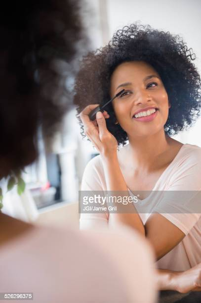 smiling woman applying mascara in mirror - mid adult stock pictures, royalty-free photos & images