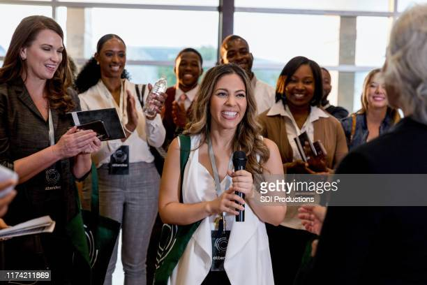 smiling woman asks question during conference - summit meeting stock pictures, royalty-free photos & images