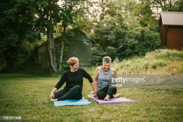 smiling woman assisting friend while exercising on mat in public park - 60 64 years stock pictures, royalty-free photos & images