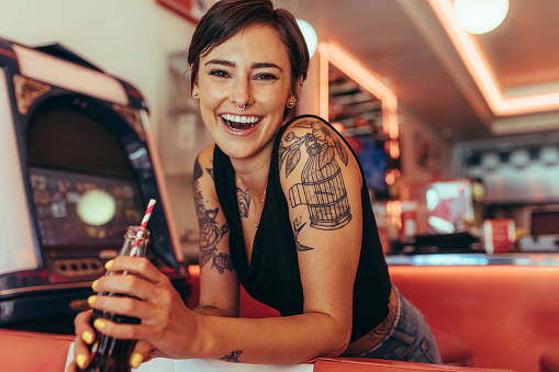 Smiling woman at a diner drinking soft drink 1053101330