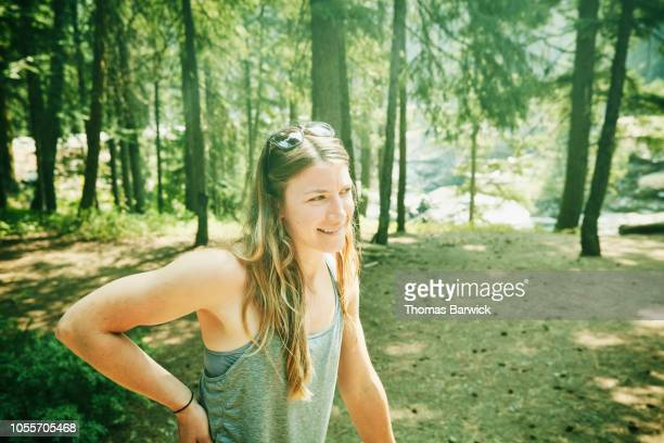 smiling woman at campsite in forest during road trip with friends - sleeveless top stock photos and pictures