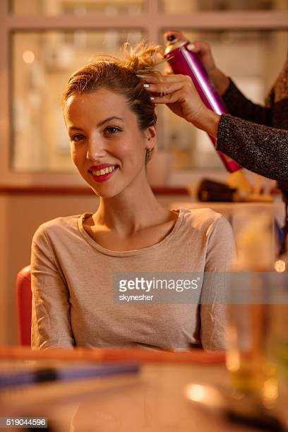 Smiling woman at hairdresser's getting her hair styled.