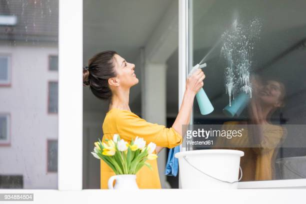 smiling woman at home cleaning the window - cleaning stock pictures, royalty-free photos & images