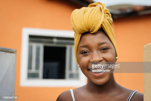 smiling woman at home entrance - turban stock pictures, royalty-free photos & images