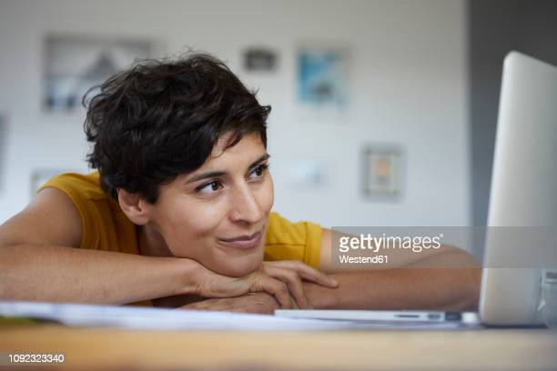 smiling woman at home leaning on table looking at laptop - nose piercing stock pictures, royalty-free photos & images