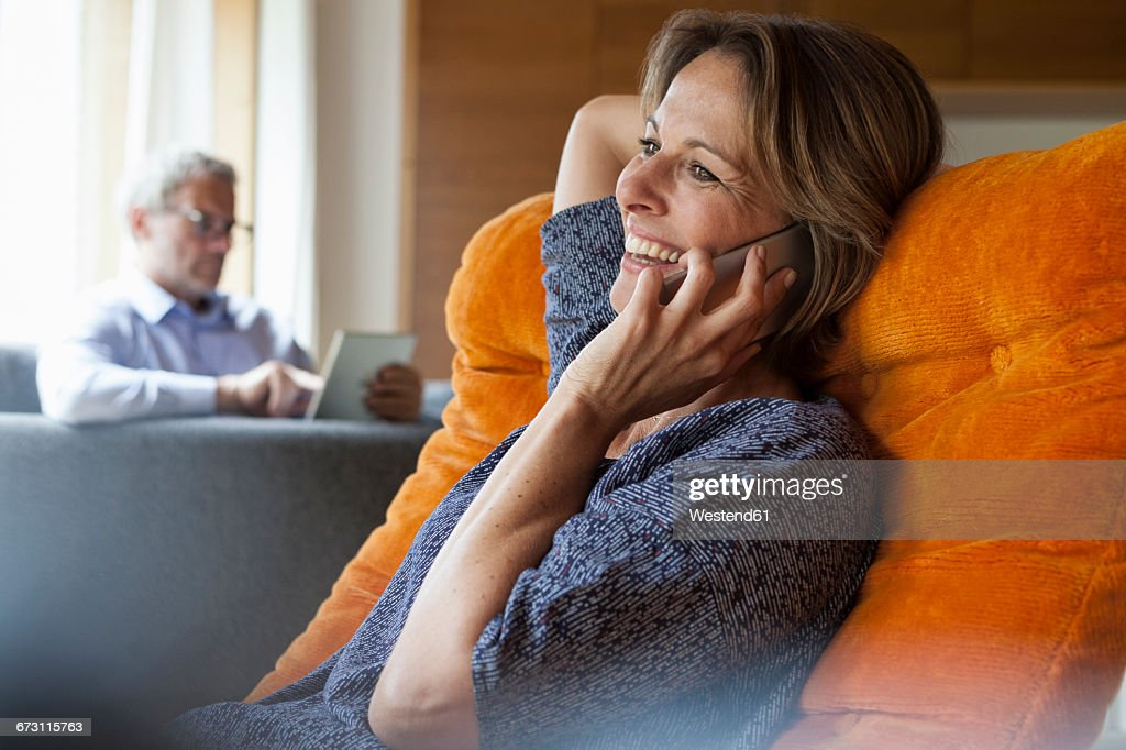 Smiling woman at home on cell phone with husband in background : Stock Photo