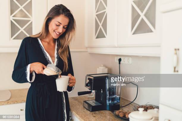 smiling woman at home preparing coffee in the morning - coffee maker stock pictures, royalty-free photos & images