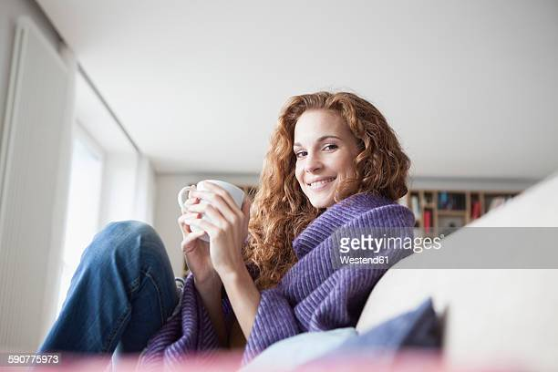 smiling woman at home sitting on couch holding cup - hot tea stock pictures, royalty-free photos & images
