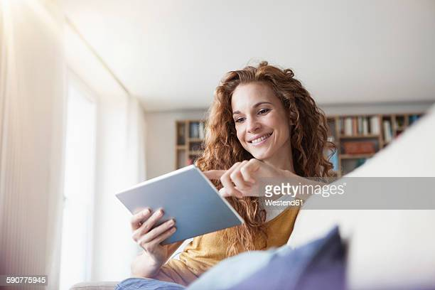 smiling woman at home sitting on couch using digital tablet - pc ultramobile foto e immagini stock
